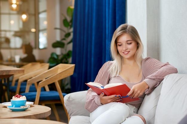 Tevreden blondemeisje die interessante boekzitting in koffie lezen.