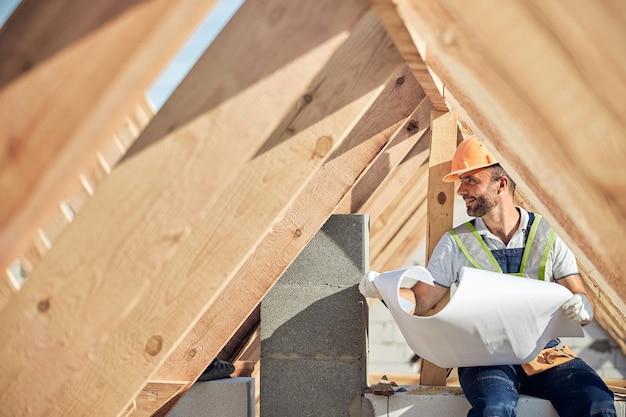 Tevreden bouwer die een helm draagt en een blauwdruk vasthoudt terwijl hij naar de bouwplaats kijkt