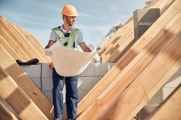 Tevreden bouwer die een helm draagt terwijl hij een blauwdruk vasthoudt en naar het houten dak kijkt