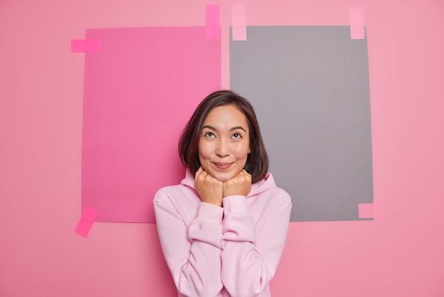 Tevreden brunette aziatische vrouw foto's iets in gedachten stelt zich een aangename scène voor houdt handen onder de kin kijkt naar boven gekleed in sweatshirt poseert tegen roze muur gepleisterde vellen papier