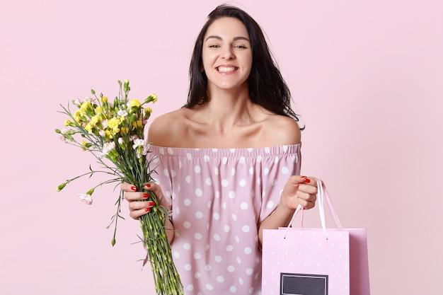Tevreden brunette europese dame houdt cadeauzakje en bloemen vast, ontvangt graag cadeau op vrouwendag, gekleed in een jurk met stippen, toont blote schouders, heeft een positieve uitstraling, poseert binnen.