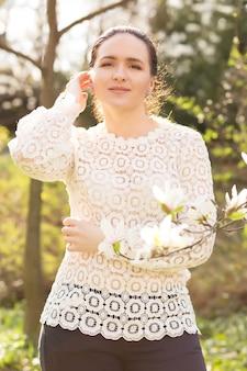 Tevreden brunette model met naakte make-up, kanten blouse dragend, poserend in de buurt van de bloeiende magnoliabloemen