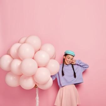 Tevreden brunette vrouw met twee vlechten, stijlvolle pet, paarse losse sweatshirt en roze rok, houdt helium ballonnen