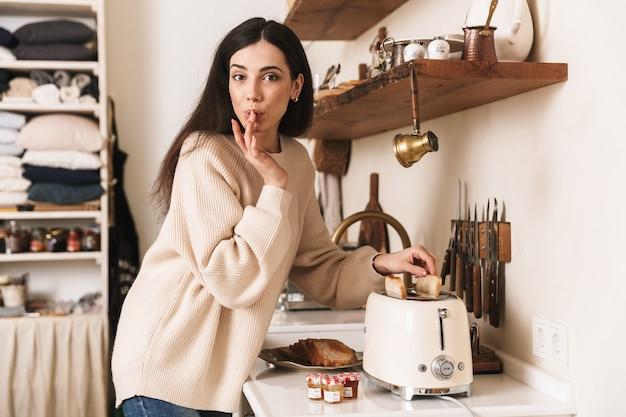 Tevreden brunette vrouw ontbijt met toast en jam in de keuken thuis maken