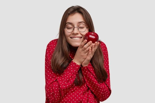 Tevreden brunette vrouw voelt plezier, houdt smakelijke appel vast, is in hoge geest, draagt rode kleren