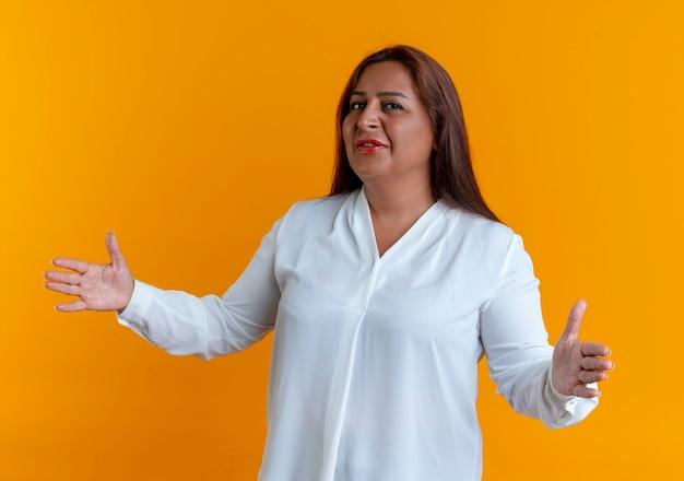 Tevreden casual blanke vrouw van middelbare leeftijd die grootte toont die op geel wordt geïsoleerd
