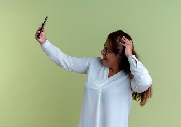 Tevreden casual blanke vrouw van middelbare leeftijd neemt een selfie en legt de hand op het hoofd