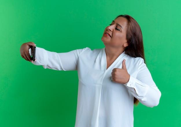 Tevreden casual blanke vrouw van middelbare leeftijd neemt een selfie met haar duim omhoog