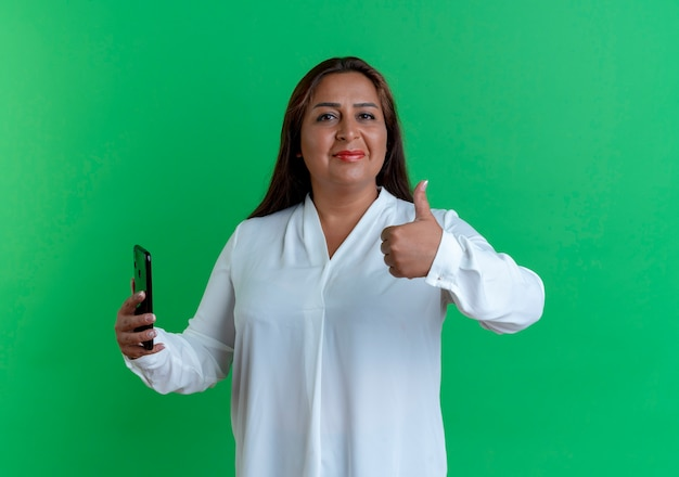 Tevreden casual kaukasische vrouw op middelbare leeftijd met telefoon haar duim omhoog