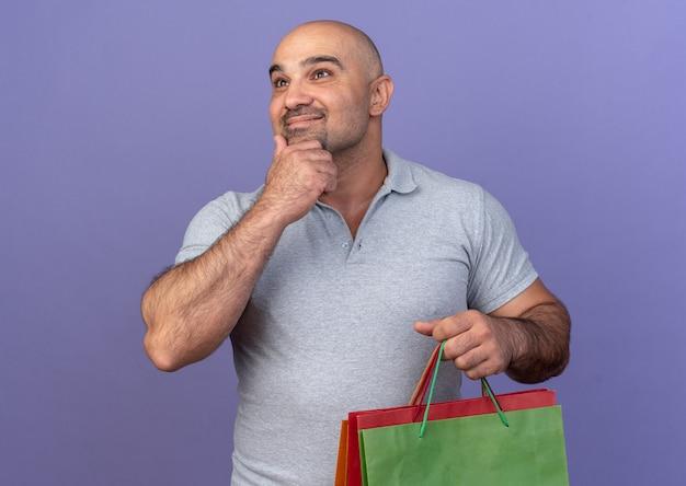 Tevreden, casual man van middelbare leeftijd die de hand op de kin houdt en boodschappentassen vasthoudt, kijkend naar de zijkant geïsoleerd op de paarse muur