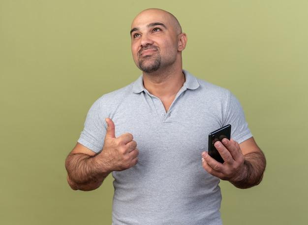 Tevreden casual man van middelbare leeftijd die mobiele telefoon vasthoudt en omhoog kijkt met duim omhoog geïsoleerd op olijfgroene muur