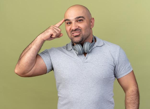 Tevreden casual man van middelbare leeftijd met een koptelefoon op de nek die naar de voorkant kijkt en een denkgebaar doet geïsoleerd op een olijfgroene muur