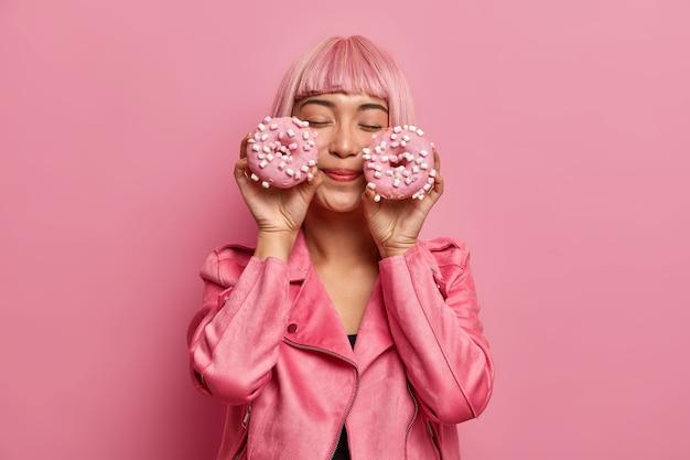 Tevreden charmante vrouw met roze haar en pony, sluit de ogen, stelt zich een aangename smaak van donuts voor, gekleed in een roze jasje