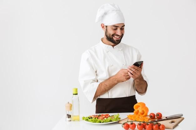 Tevreden chef-kok man in uniform glimlachend en smartphone vast te houden tijdens het koken van groentesalade geïsoleerd over witte muur