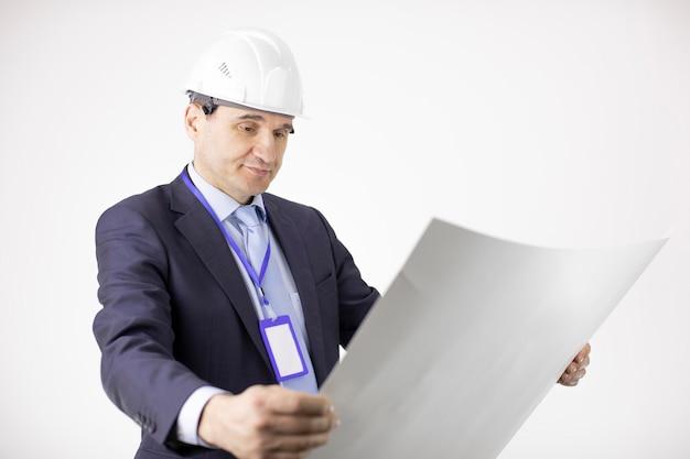 Tevreden cheif-ingenieur in veiligheidshelm die met blauwdrukdocumenten werkt