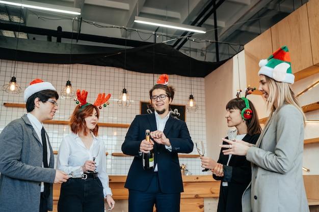 Tevreden collega's in kantoor vieren speciale gebeurtenis samen, glimlachend divers werkteam veel plezier lachen. vriendschap concept