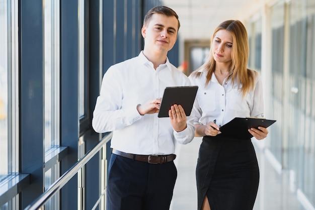 Tevreden collega's in moderne kantoren met behulp van tablet