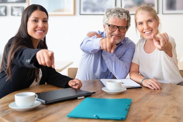 Tevreden collega's of partners poseren en wijzend op de camera zittend aan tafel met koffiekopjes en documenten
