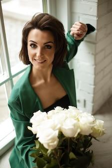 Tevreden dame in een groen kostuum staat bij het raam met prachtige witte rozen. stijl en mode-concept
