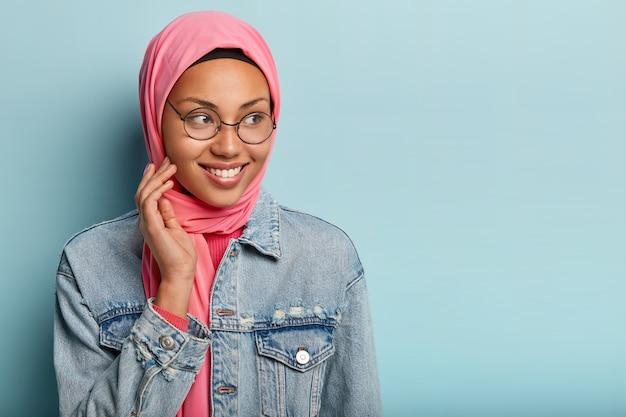 Tevreden dame met donkere huid heeft islamitische opvattingen, draagt een transparante bril