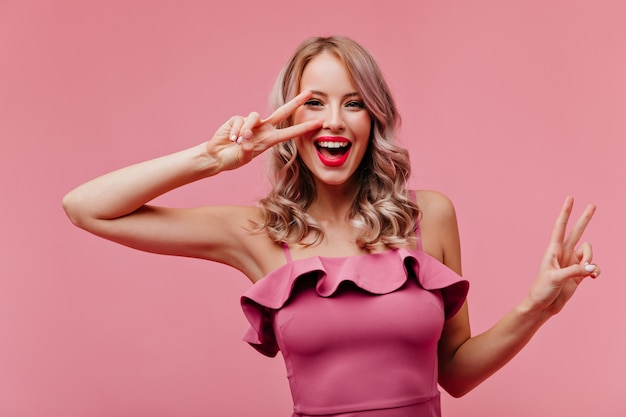 Tevreden dame met romantisch kapsel dat op roze muur lacht