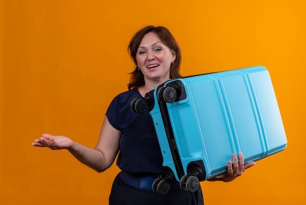 Tevreden de holdingskoffer en punten van de reizigersvrouw op middelbare leeftijd met hand aan kant op geïsoleerde oranje achtergrond