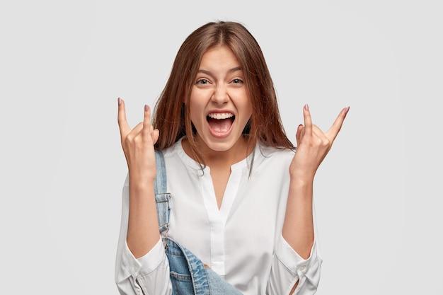 Tevreden dolblij jonge brunette vrouw toont rock gebaar, proost en viert iets