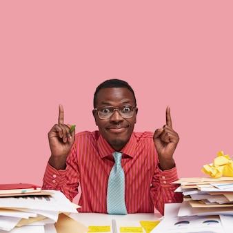 Tevreden donkere man zoekt creatieve soultion voor het verbeteren van project, neemt een beslissing, heeft stapel documenten op bureau