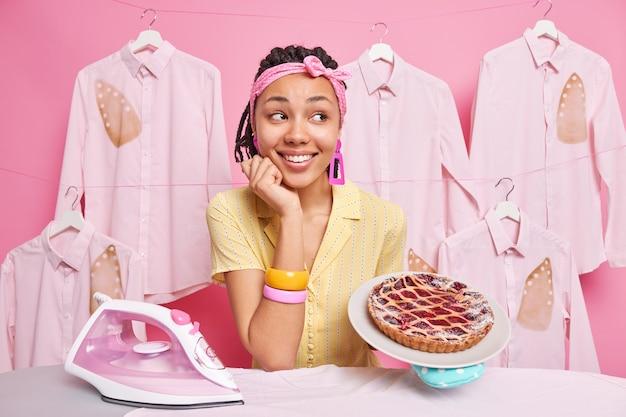 Tevreden donkere multitasking huisvrouw bakt taart en strijkt kleding voor familie draagt hoofdband armbanden poseert in de buurt van strijkplank glimlacht vrolijk poseert tegen roze muur
