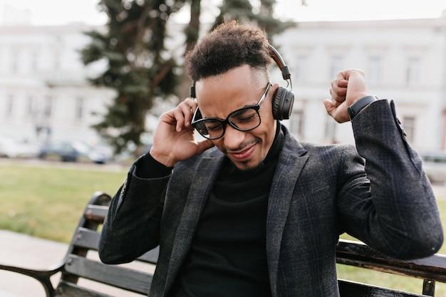 Tevreden donkerharige afrikaanse man draagt zwarte kleren die buiten koelen. foto van ontspannen mulat man in glazen genieten van muziek in koptelefoon.