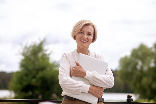 Tevreden elegante dame met een notebook die vooruitkijkt
