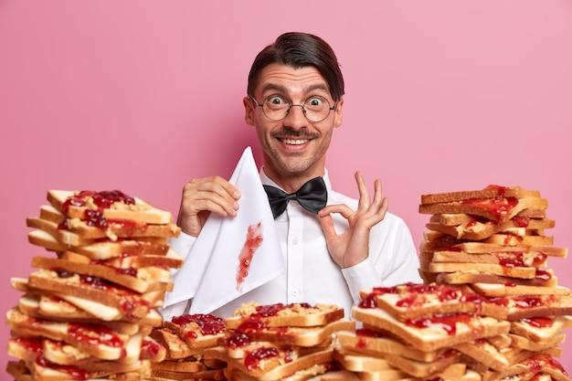 Tevreden elegante man cafébezoeker past vlinderdas aan, hongerig en klaar voor het eten van heerlijke toast met jam, houdt servet vast, heeft beleefde manieren, geïsoleerd op roze muur. mensen, eten concept