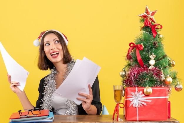 Tevreden emotionele geconcentreerde zakelijke dame in pak met kerstman hoed en nieuwjaarsversieringen met documenten en zittend aan een tafel met een kerstboom erop in het kantoor