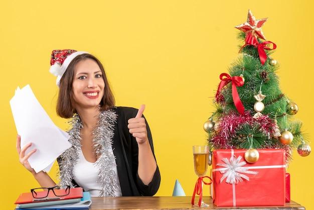 Tevreden emotionele zakelijke dame in pak met kerstman hoed en nieuwjaarsversieringen houden documenten ok gebaar maken en zitten aan een tafel met een kerstboom erop in het kantoor