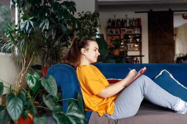 Tevreden en gelukkig lachend meisje zittend op de bank in de kamer en schrijft een dagboek van je dromen, plannen, doelen, ervaringen, ideeën, geleefde emoties en gevoelens. lifestyle, huisplannen, woonkamer