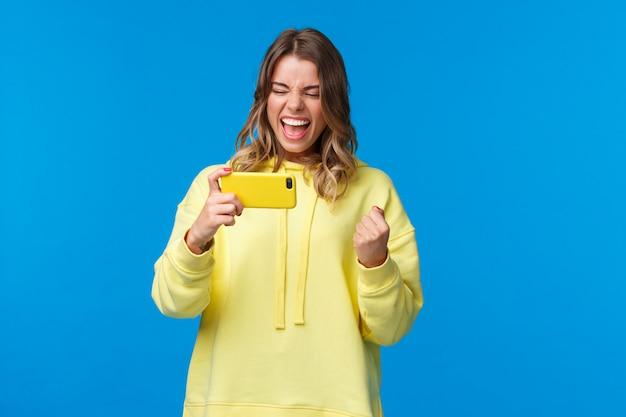 Tevreden en tevreden zegevierend jong meisje dat online livestream van spel op internet bekijkt met behulp van mobiele telefoon, wint, roott voor het gescoorde teamdoel, ja verheugd zegt,