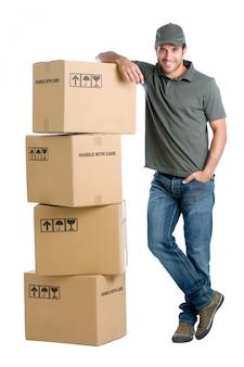 Tevreden en trotse leveringsmens die op een stapel dozen leunt die op witte achtergrond worden geïsoleerd