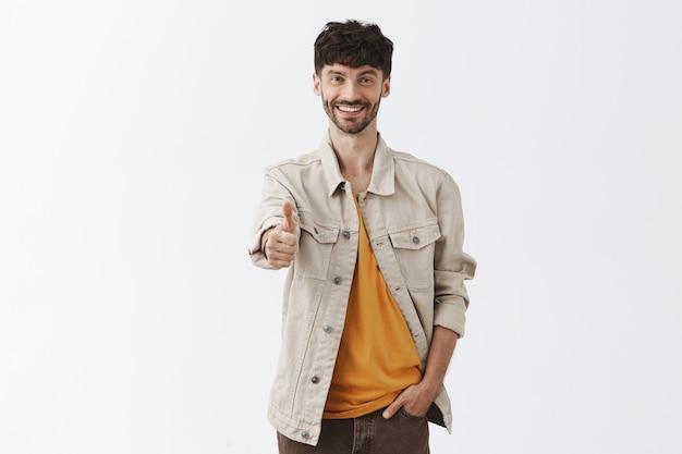 Tevreden en zelfverzekerd stijlvolle bebaarde man poseren tegen de witte muur