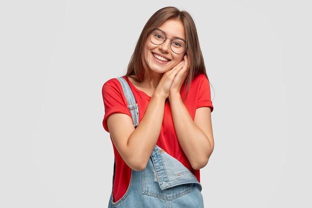 Tevreden europese jonge vrouw met vrolijke uitdrukking, houdt beide handen dicht bij het gezicht, aangeraakt door compliment