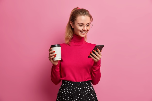Tevreden europese vrouw met paardenstaart geniet van een geweldige applicatie op de smartphone
