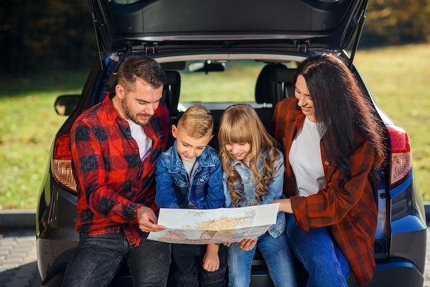 Tevreden familie van knappe vader, mooie moeder en lieve kinderen die op de wegenkaart kijken terwijl ze in de kofferbak van de auto zitten.