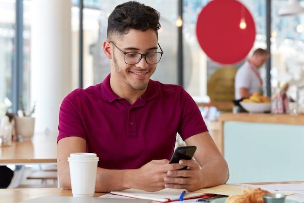 Tevreden freelancer werkt online, is mobiel, stuurt sms-berichten op sociale netwerken, zit in een restaurant. student wisselt notificaties uit met groepsgenoot, bereidt zich voor op seminar, schrijft notities