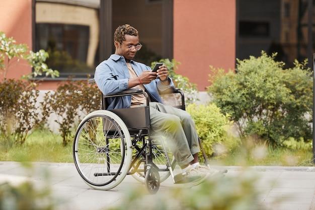 Tevreden gehandicapte afro-amerikaanse man die in een rolstoel op straat zit en een bericht op de telefoon leest terwijl hij online aan het chatten is