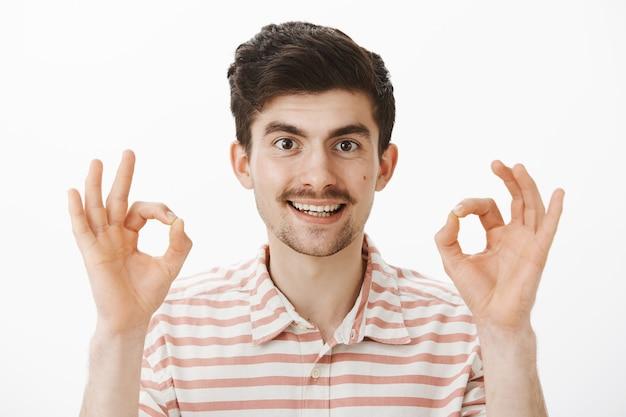 Tevreden geïnteresseerde aantrekkelijke man met snor, vingers opsteken en ok of ok gebaar laten zien, goede suggestie goedkeuren, probleem graag oplossen, alles onder controle hebben