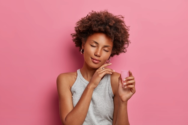 Tevreden gekrulde vrouw raakt gezicht met plezier aan, staat met gesloten ogen, houdt flexibele menstruatiecup vast om tijdens menstruatie in de vagina in te brengen, beschermt tegen bloedlekkage, geïsoleerd op roze muur