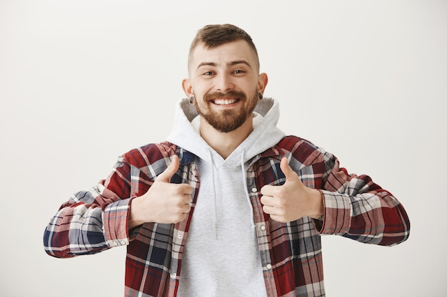 Tevreden gelukkig glimlachende man die duimen toont, goed werk prijst, goed gedaan