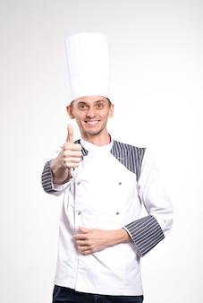 Tevreden gelukkig jonge chef-kok poseren geïsoleerd op witte muur achtergrond in uniform.