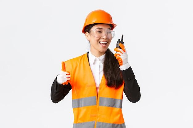 Tevreden, gelukkig lachende aziatische vrouwelijke ingenieur, industrieel technicus in veiligheidshelm en uniform die duimen omhoog laat zien terwijl hij geweldig werk prees met behulp van walkie-talkie, toestemming geeft om te werken