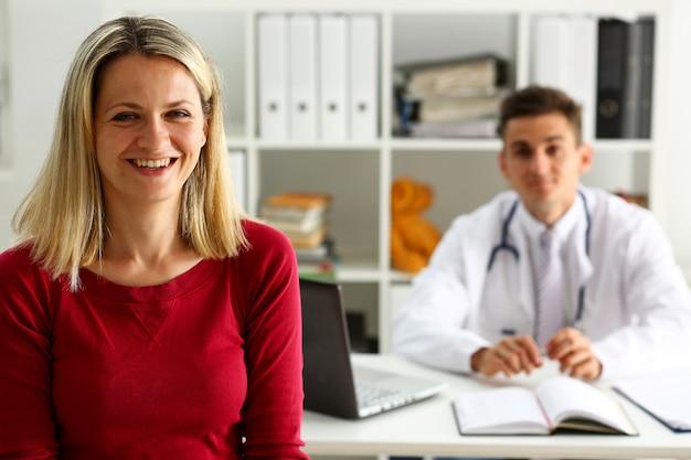 Tevreden gelukkig mooie glimlachende vrouwelijke patiënt met arts