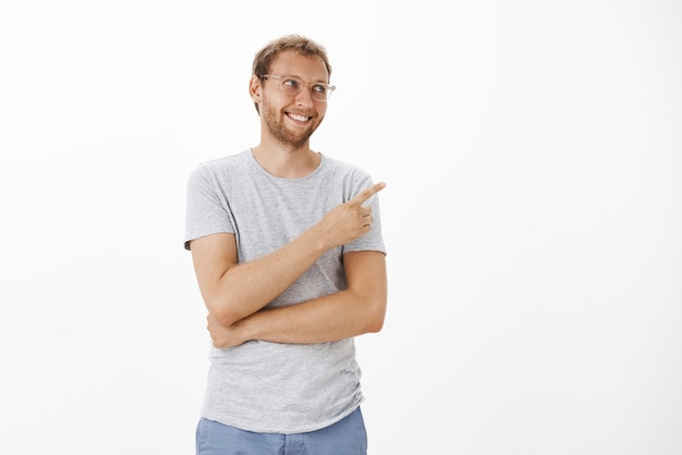 Tevreden gelukkig schattig europees mannelijk model in glazen met varkenshaar en blond haar glimlachend vrolijk wijzend en starend naar de rechterbovenhoek met opgetogen uitdrukking